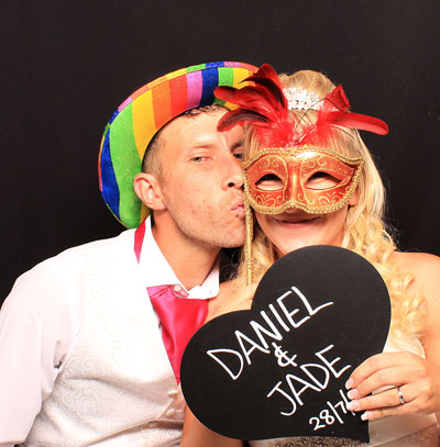 couple in the photo booth with love heart board