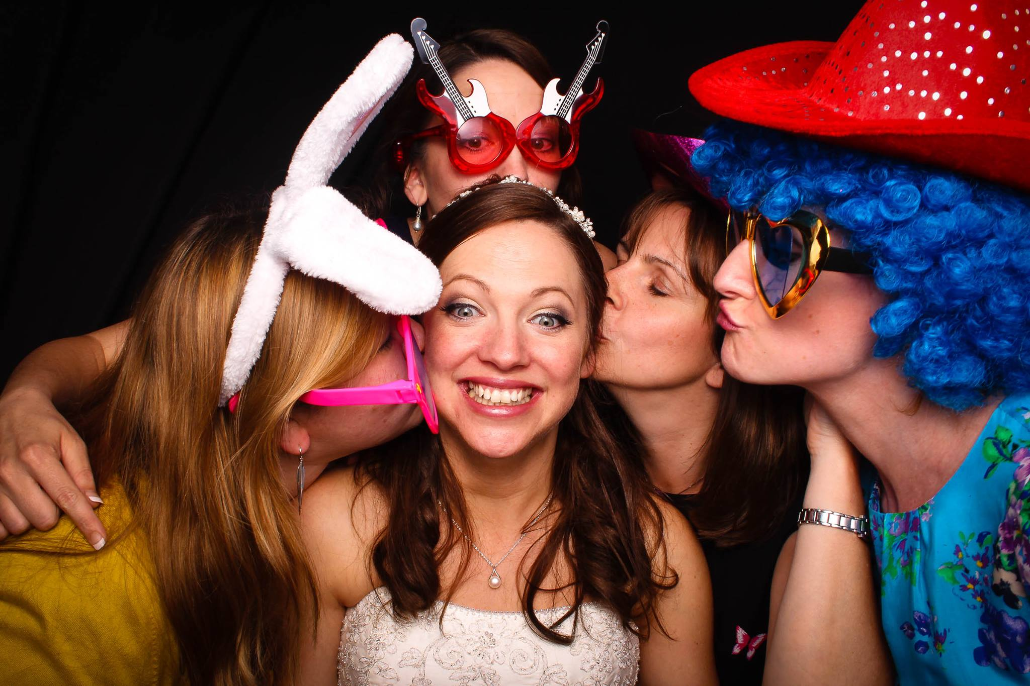 Lovely Bride surrounded by with guests in the photo booth